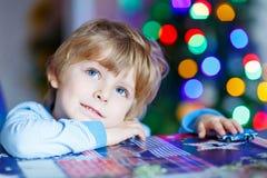 Kleines blondes Kind, das zu Hause mit Autos und Spielwaren spielt Stockfoto