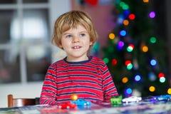 Kleines blondes Kind, das zu Hause mit Autos und Spielwaren spielt Lizenzfreies Stockfoto
