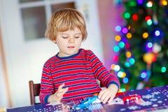 Kleines blondes Kind, das zu Hause mit Autos und Spielwaren spielt Lizenzfreie Stockfotos