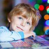 Kleines blondes Kind, das zu Hause mit Autos und Spielwaren spielt Stockbilder