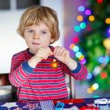 Kleines blondes Kind, das zu Hause mit Autos und Spielwaren spielt Stockbild