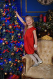 Kleines blondes Kind in einem roten Kleid Stockbilder