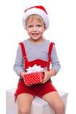 Kleines blondes Kind im roten Kostüm der zwergartigen haltenen Geschenkbox mit Band Weihnachten Lizenzfreies Stockfoto