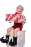 Kleines blondes Kind im roten Kostüm des Zwergs große Geschenkbox mit Band halten Weihnachtsniederlassung und -glocken Stockfoto
