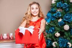 Kleines blondes Kind mit dem überraschten Gesicht, roten Kasten mit weißem Knoten an der Kamera zeigend Lizenzfreie Stockfotografie