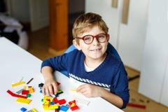 Kleines blondes Kind mit den Augengläsern, die mit vielen bunten Plastikblöcken spielen Stockfoto