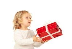 Kleines blondes Kind mit einem roten Geschenk Stockfotografie