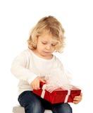 Kleines blondes Kind mit einem roten Geschenk Stockfotos