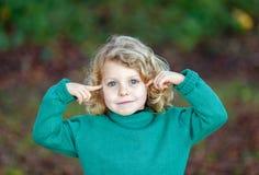 Kleines blondes Kind mit grünem Trikot etwas vorstellend Stockfotografie