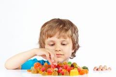 Kleines blondes Kind mit Süßigkeiten auf weißem Hintergrund Stockbild