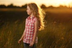 Kleines blondes Kindermädchen, das auf dem Sommergebiet bei Sonnenuntergang steht Lizenzfreie Stockfotos