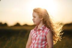 Kleines blondes Kindermädchen, das auf dem Sommergebiet bei Sonnenuntergang steht Lizenzfreies Stockfoto