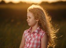 Kleines blondes Kindermädchen, das auf dem Sommergebiet bei Sonnenuntergang steht Stockfoto