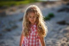 Kleines blondes Kindermädchen, das in Sommerstrand bei Sonnenuntergang geht Stockfotografie