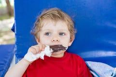 Kleines blondes Kleinkind, das SchokoladenEiscreme isst Stockbild