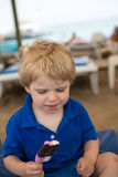 Kleines blondes Kleinkind, das SchokoladenEiscreme isst Lizenzfreies Stockfoto
