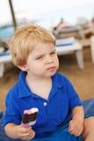 Kleines blondes Kleinkind, das SchokoladenEiscreme isst Stockbilder