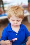 Kleines blondes Kleinkind, das SchokoladenEiscreme isst Lizenzfreie Stockfotografie