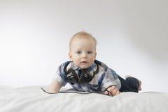 Kleines blondes Kleinkind mit Kopfhörern Stockbilder