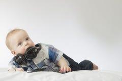 Kleines blondes Kleinkind mit Kopfhörern auf seinem Hals Stockfotos