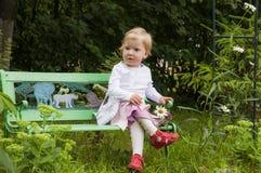Kleines blondes Kleinkindmädchen auf einer Bank Lizenzfreie Stockfotografie