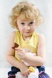 Kleines blondes lockiges Mädchen, das Schokolade isst Lizenzfreies Stockbild