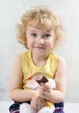 Kleines blondes lockiges Mädchen, das Schokolade isst Lizenzfreie Stockbilder