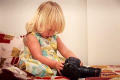 kleines blondes Mädchen überprüft Kamera gegen weiße Wand Lizenzfreies Stockbild