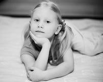 Kleines blondes Mädchen auf dem Bett Stockbilder