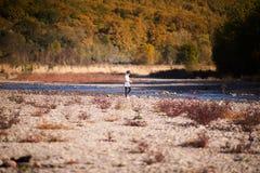 Kleines blondes Mädchen auf dem Flussufer Herbst im gelben Wald Stockbild