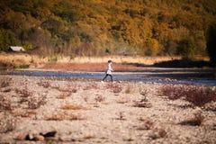 Kleines blondes Mädchen auf dem Flussufer Herbst im gelben Wald Lizenzfreie Stockfotos