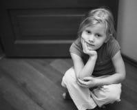 Kleines blondes Mädchen auf dem Fußboden Stockfotos