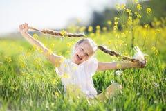 Kleines blondes Mädchen auf dem gelben Gebiet mit Blumen Lizenzfreies Stockbild
