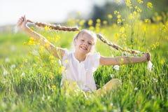 Kleines blondes Mädchen auf dem gelben Gebiet mit Blumen Lizenzfreie Stockbilder