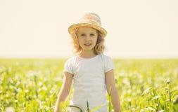 Kleines blondes Mädchen auf einem Weizengebiet Lizenzfreie Stockfotos