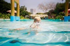 kleines blondes Mädchen badet Lachen im transparenten Wasser des Pools Stockfotografie