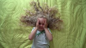 Kleines blondes Mädchen, das auf Bett- und Spielfellsuchvorgang liegt Draufsicht der Kardanringbewegung stock video