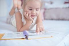 Kleines blondes Mädchen, das auf dem Bett liest ein Buch liegt Stockbild
