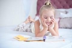 Kleines blondes Mädchen, das auf dem Bett liest ein Buch liegt Stockfotografie