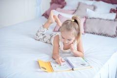Kleines blondes Mädchen, das auf dem Bett liest ein Buch liegt Lizenzfreie Stockbilder