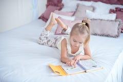 Kleines blondes Mädchen, das auf dem Bett liest ein Buch liegt Lizenzfreies Stockfoto
