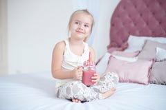 Kleines blondes Mädchen, das auf dem Bett liest ein Buch sitzt Stockfoto