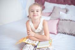 Kleines blondes Mädchen, das auf dem Bett liest ein Buch sitzt Lizenzfreies Stockbild