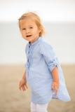 Kleines blondes Mädchen, das auf dem Strand spielt Lizenzfreie Stockfotos