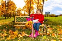 Kleines blondes Mädchen, das auf der Bank im Park sitzt Stockfotografie