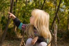 Kleines blondes Mädchen, das auf die Seite zeigt Stockbilder