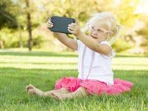 Kleines blondes Mädchen, das draußen Selfie mit intelligentem Telefon nimmt Stockfotografie