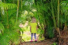 Kleines blondes Mädchen, das draußen unter Palmen bleibt Stockfotografie
