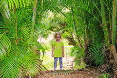 Kleines blondes Mädchen, das draußen unter Palmen bleibt Lizenzfreie Stockfotografie