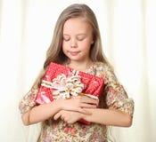 Kleines blondes Mädchen, das ein rotes bezauberndes Geschenk anhält Lizenzfreie Stockbilder